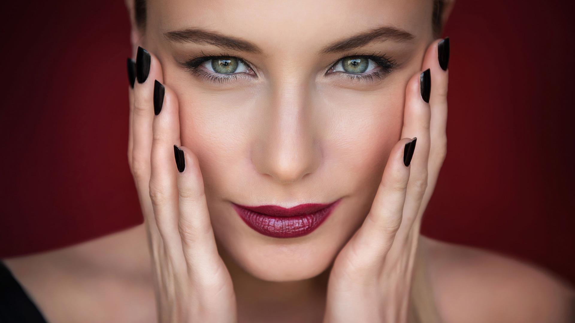 Junge Frau mit dunkelroten Lippen und schwarzen Fingernägeln